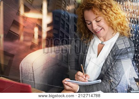 Talented person. Beautiful curly-haired woman sitting in the coffee house and writing poems in her notebook while smiling peacefully and happily