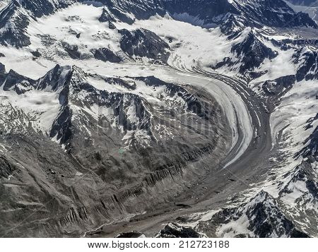 Huge High Mountains Glacier: The Moraine Ice Tongue Curves Among The Snow-capped Mountain Peaks And