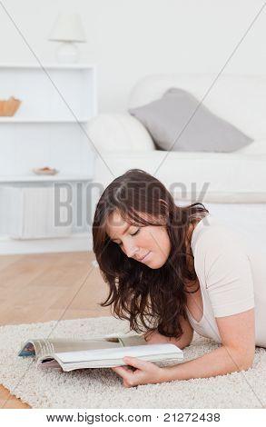 Junge hübsche Frau, die eine Zeitschrift lesen, beim liegen auf einem Teppich
