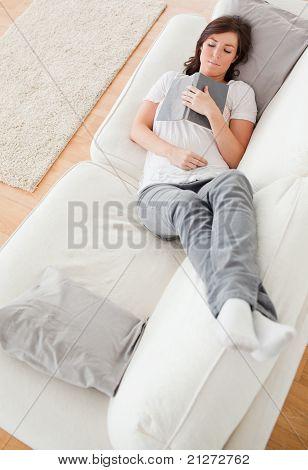 Junge Cute Female erholend und ein Buch zu lesen, beim liegen auf dem Sofa