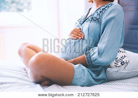 Beautiful pregnant woman holds hands on belly in bedroom at home. Young mother waiting of a baby. Concept of pregnancy maternity health care gynecology medicine. Close-up indoors.