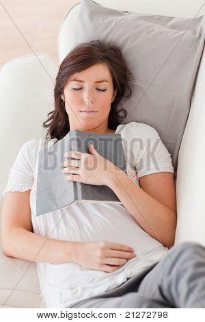 Junge schöne weibliche erholend und ein Buch zu lesen, beim liegen auf dem Sofa