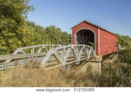 The red Wolf Covered Bridge with pony truss approaches crosses the Spoon River in rural Knox County Illinois.