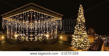 Engraved Christmas tree and pergola on the terrace of the house. Ornate and lighted Christmas tree in the garden. Xmas tree and lighting of the house at Christmas time