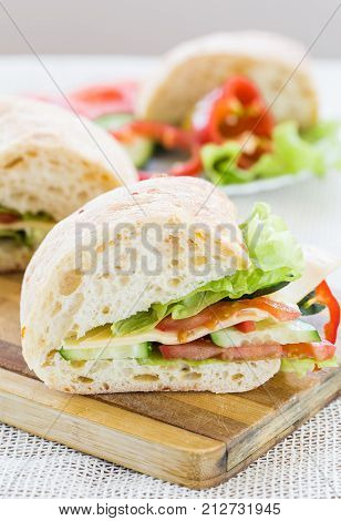Ciabatta Sandwich with cheese on cutting board, vertical view