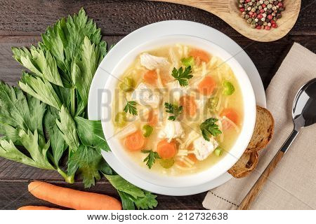 A closeup photo of a plate of chicken and noodles soup, shot from above on a dark rustic texture with a spoon, a wooden ladle with peppercorns, slices of bread, a celery branch, and a carrot