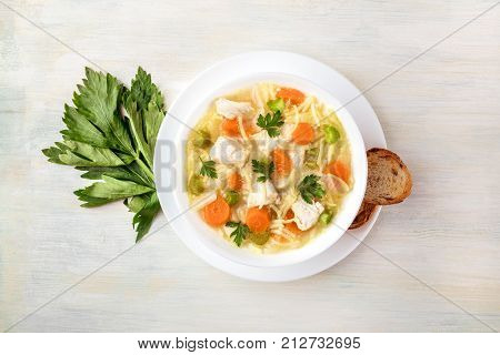 An overhead photo of a plate of chicken, vegetables, and noodles soup, shot from above on a light wooden texture with slices of bread, a celery branch, and a place for text