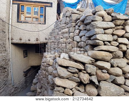 Stone fence a masonry of gray oval stones in the background a white Tibetan house with a traditional window in the glass a blue sky with clouds is reflected Ladakh India.