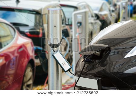 Many electric car are charged by charging stations in the parking lot.