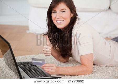 Young Gorgeous Woman Making A Payment With A Credit Card On The Internet While Lying On A Carpet