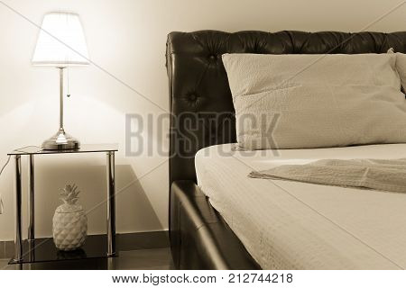 bedroom with double bed and table lamp sepia toning