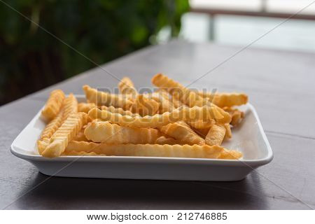 French Fries In A White Plate On A Wooden Table.