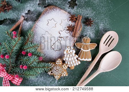 Christmas and holiday baking background. Fir trees with decoration flour spices and cookies molds on a cutting board. Beautiful cookies with décor on green background.