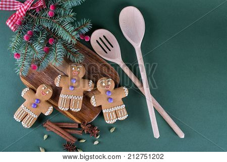 Christmas and holiday baking . Ginger men cookies with décor on green background.