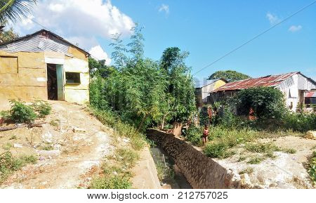 SANTO DOMINGO, DOMINICAN REPUBLIC - OCT 25, 2015: Poor little boy at the edge of a ditch between hovels in Santo Domingo, Dominican Republic.