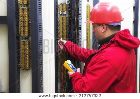 Engineer in red control circuit with multimeter in power plant