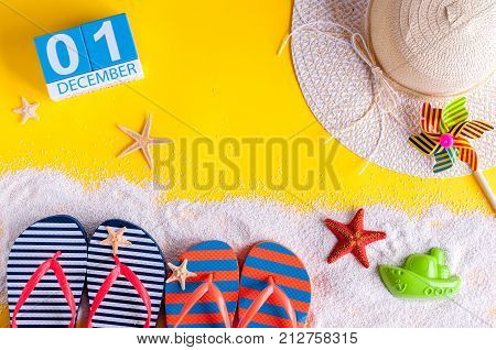 December 1st. Image of december 1 calendar with summer beach accessories and traveler outfit on background. Winter like Summer vacation concept.