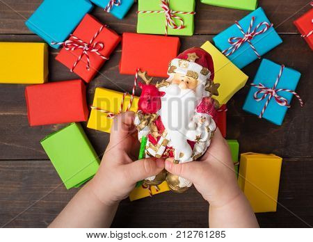 Two Child Hands Hold Santa Claus Toy With Hope For Presents