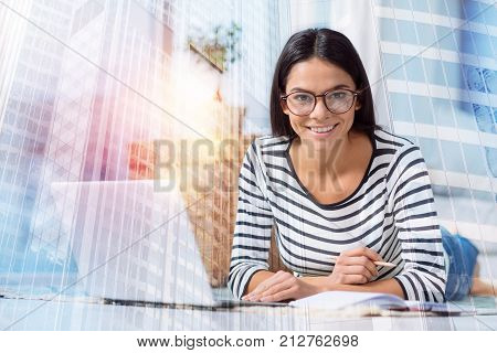 Smart woman. Friendly cheerful enthusiastic manager smiling and looking glad while working at home with a laptop by her side