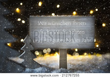 Sign With German Text Wir Wuenschen Ihnen Frohe Weihnachten Und Ein Gutes Neues Jahr Means We Wish You A Merry Christmas And A Happy New Year. White Christmas Tree With Snow And Lights.