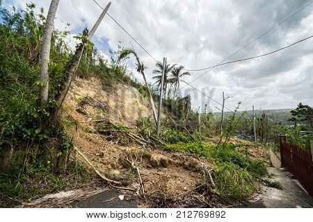 Roadway covered with mudslide from saturated hillside along highway in Puerto Rico