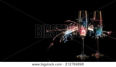 Two tall glasses of champagne in multicolored Bengal lights. Black background. Silhouette. The concept of celebration. New Year celebration.