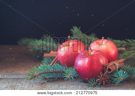 Christmas apples with cinnamon and badyan with branches of Christmas-tree. Toned. Snowflakes