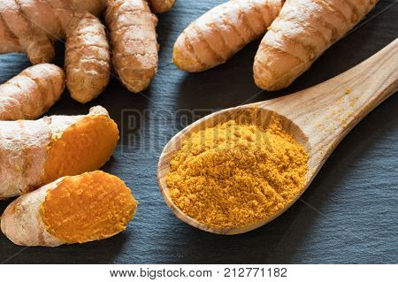 Turmeric Powder On A Wooden Spoon, With Fresh Turmeric Root In The Background