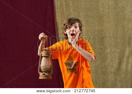 Surprised young actor holds kerosene lamp and places one hand on face
