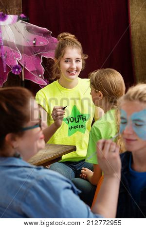 Young acting camp assistant smiles at camera as she helps child actor prepare for production