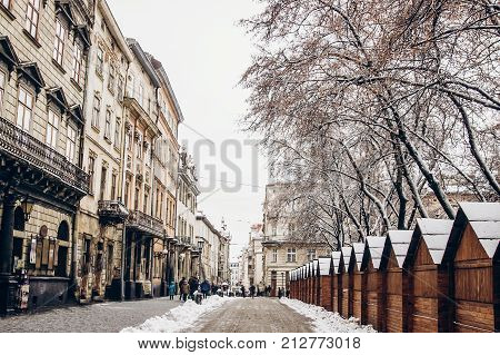 Beautiful City Center And Wooden Cabins For Market Covered In Snow. Snowy Town Square In Lviv. Europ