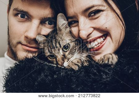 Happy Stylish Hipster Family Hugging With Their Cat. Man And Woman Holding Kitty And Having Fun And