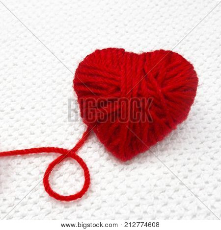 Red yarn ball like a heart and a thread loop on the white crochet background. Romantic Christmas or Valentines Day concept. Red heart made of wool yarn. Festive photo knitting with love
