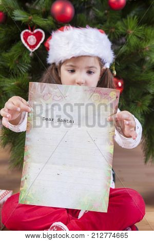 Little girl showing The Santa Letter. She painted a sheet with header in English