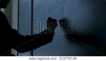 Scientist writing formulas on chalkboard. Hand with chalk wrote physics formulas on black chalkboard closeup 4K