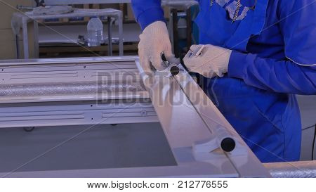 Construction worker installing window on manufacture. Manual worker assembling glass panels for PVC windows. Manufacturing jobs.Factory for aluminum and PVC windows and doors production.
