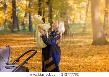 A young mother with a stroller is talking on her mobile phone while walking in the park. Walking with an infant in the open air in a pine forest. Newborn, family, child, parenthood.