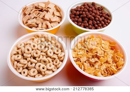 Various corn flakes in different plates, four different colored plates with flakes, pads, chocolate balls, circles, and flakes, isolated on white background