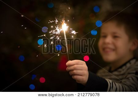 Closeup of a sparkler in hands of a happy kid boy. Christmas and Happy New Year celebration. Holidays season. Selective focus