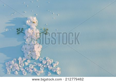 Top view on funny snowman made of white flowers petals on light blue background with sun shine. Holidays winter and Christmas concept