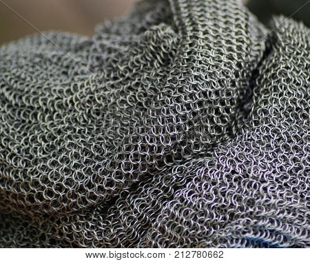 Stainless steel chain mail shirt at rest. Puddled mail resembles snake-skin.