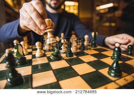a young man playing chess sitting in cafe