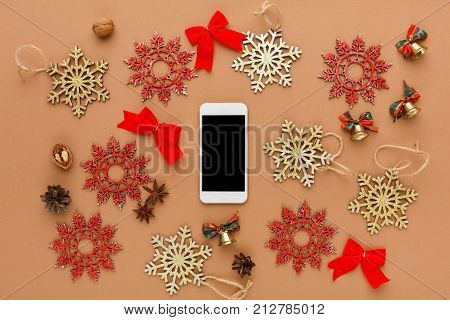 Christmas decoration, wooden snowflakes ornament and satin bows on brown background, top view. Online shopping on smartphone with copy space on screen. Preparing for winter holidays concept.