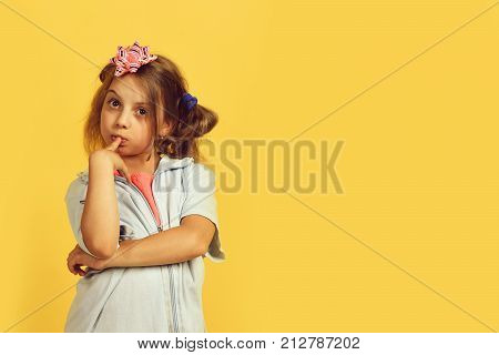 School girl and paper bow for present boxes. Girl with thinking face expression isolated on warm yellow background. Holiday and present concept. Kid with cute pink bow on head and messy hair