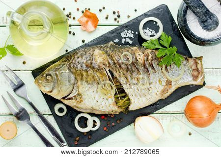 Whole fried fish on kitchen table with ingredients top view
