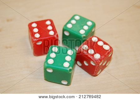 Red and green dice that have been rolled so much they are showing wear and tear.