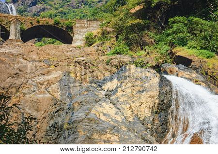 Railroad bridge over the Dudhsagar Waterfall. Falling water of the waterfall in the tropical jungle of India.