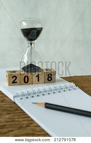 new year 2018 goals target or checklist concept as number 2018 wooden cube block with sandglass and white paper note with pencil on wooden table.