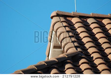 Red clay Spanish tiled roof, showing peak and edges.