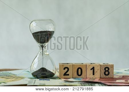 Year 2018 business time countdown or long term investment concept as hourglass or sandglass on pile of Euro banknotes with wooden cube block number 2018.